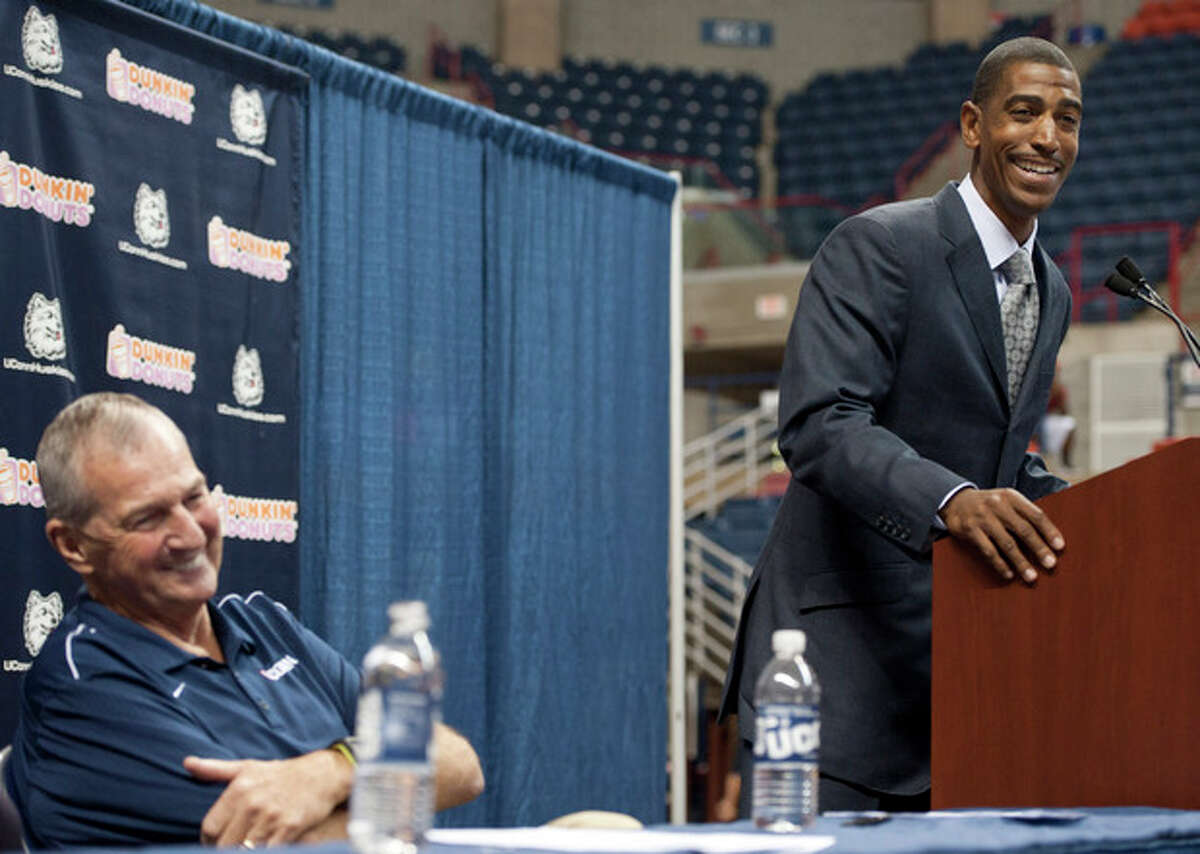New Connecticut head coach Kevin Ollie, right, smiles as retired coach Jim Calhoun looks on during a news conference announcing Calhoun's retirement, Thursday, Sept. 13, 2012, in Storrs, Conn. Ollie, an assistant coach under Calhoun, will succeed him. (AP Photo/Jessica Hill)