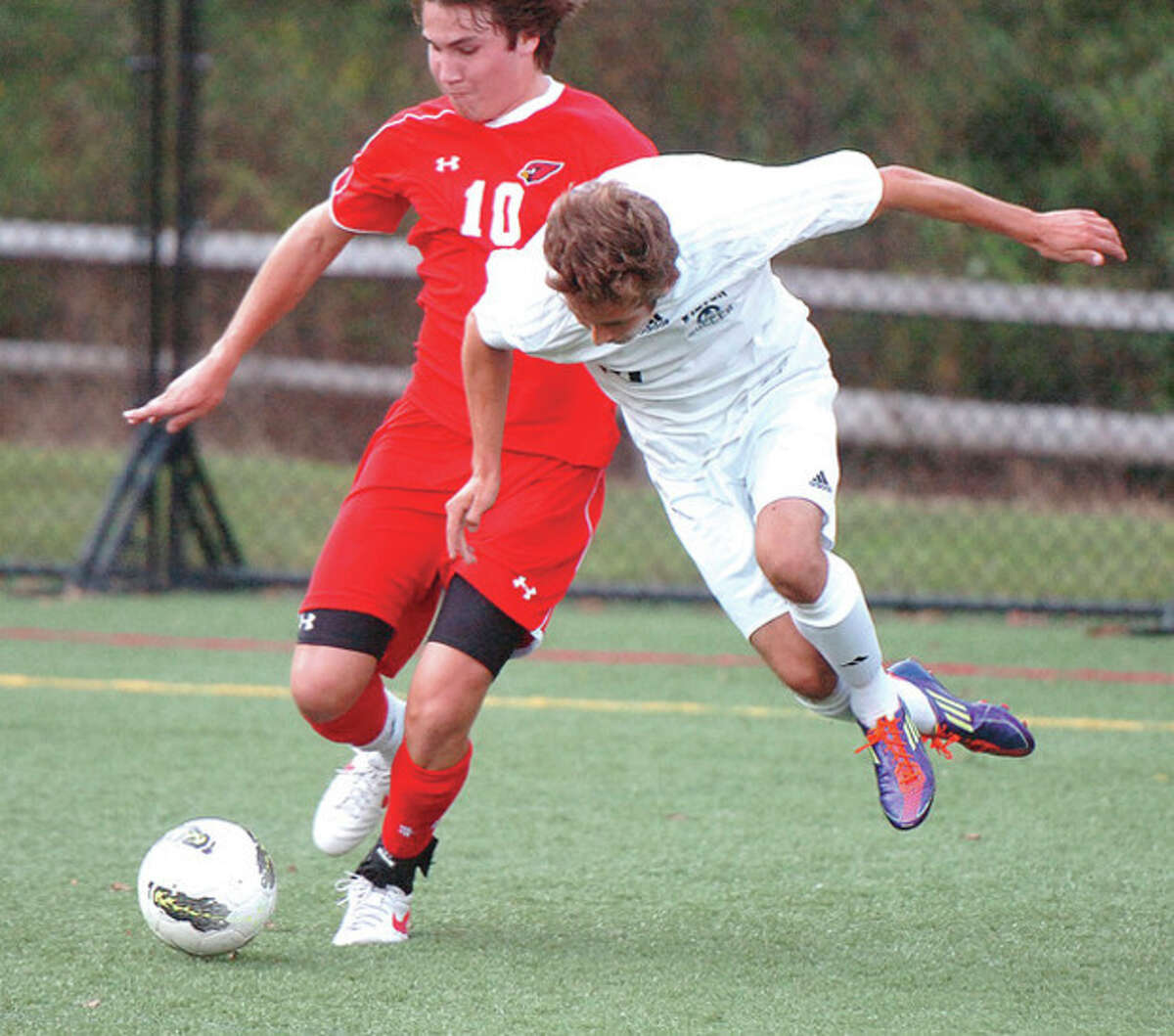 Hour photo/Alex von Kleydorff Wilton boys soccer player Robert Aravena, right, fights for possession of the ball with Greenwich's Ryan Flippin during Thursday's FCIAC game at Lilly Field. The two teams played to a 1-1 tie.