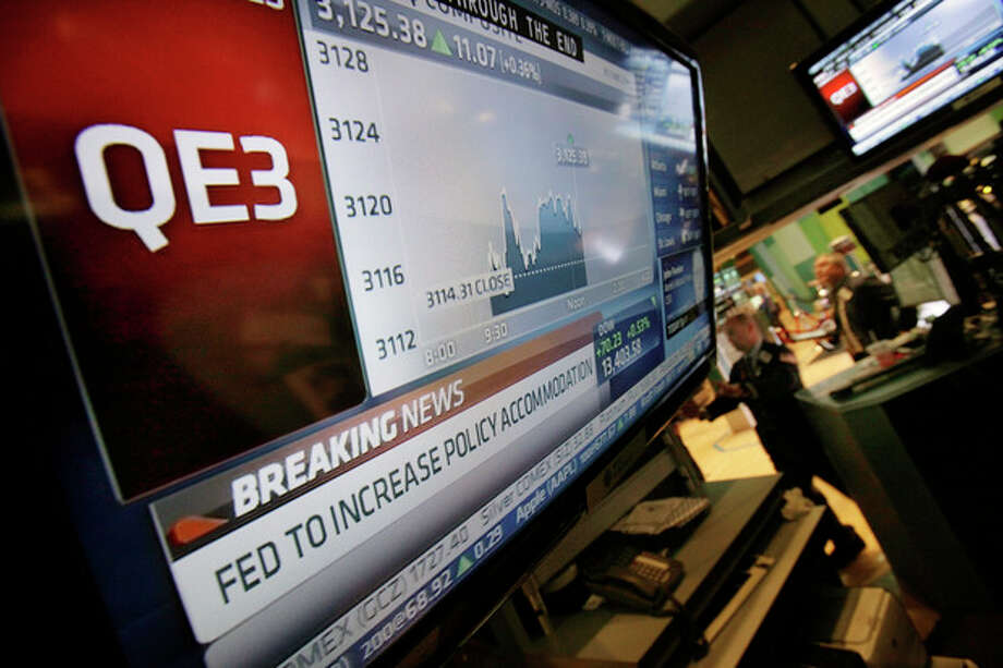 The rate decision of the Federal Reserve is announced on a television screen on the floor of the New York Stock Exchange Thursday, Sept. 13, 2012. The Federal Reserve unleashed a series of aggressive actions Thursday intended to stimulate the still-weak economy by making it cheaper for consumers and businesses to borrow and spend. (AP Photo/Richard Drew) / AP