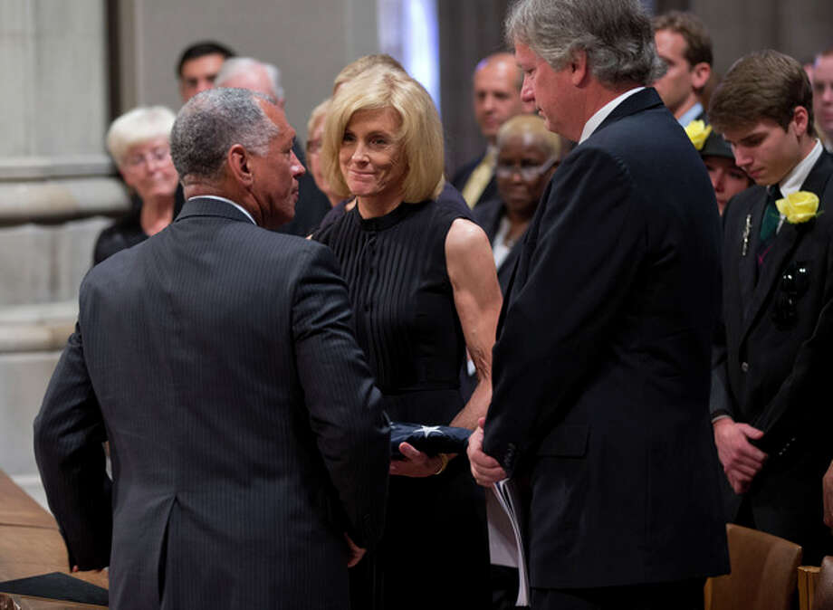 Carol Armstrong, wife of Apollo 11 astronaut Neil Armstrong is presented with a flag by NASA administrator Charles Bolden, as his son Rick Armstrong looks on at right, Thursday, Sept. 13, 2012, during a memorial service at the National Cathedral in Washington. (AP Photo/Pool, Evan Vucci, Pool) / AP POOL