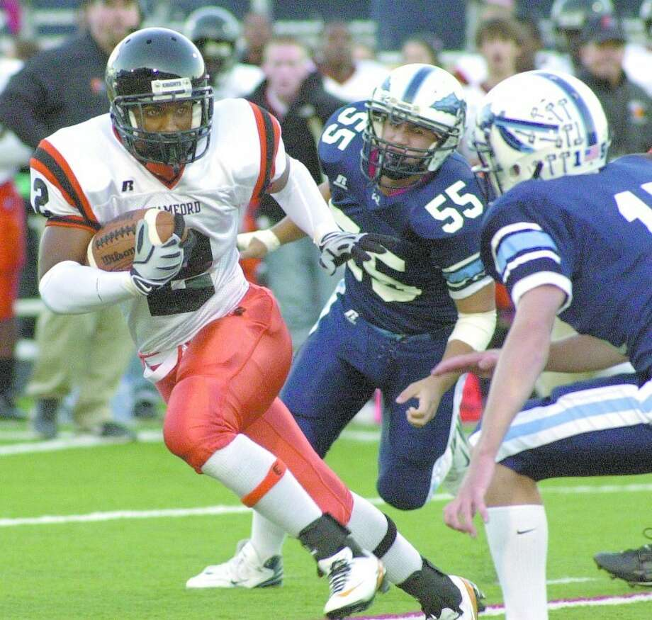 Photo by John Nash - Stamford's Marcus Dixon, left, looks for running room vs. Wilton on Friday.