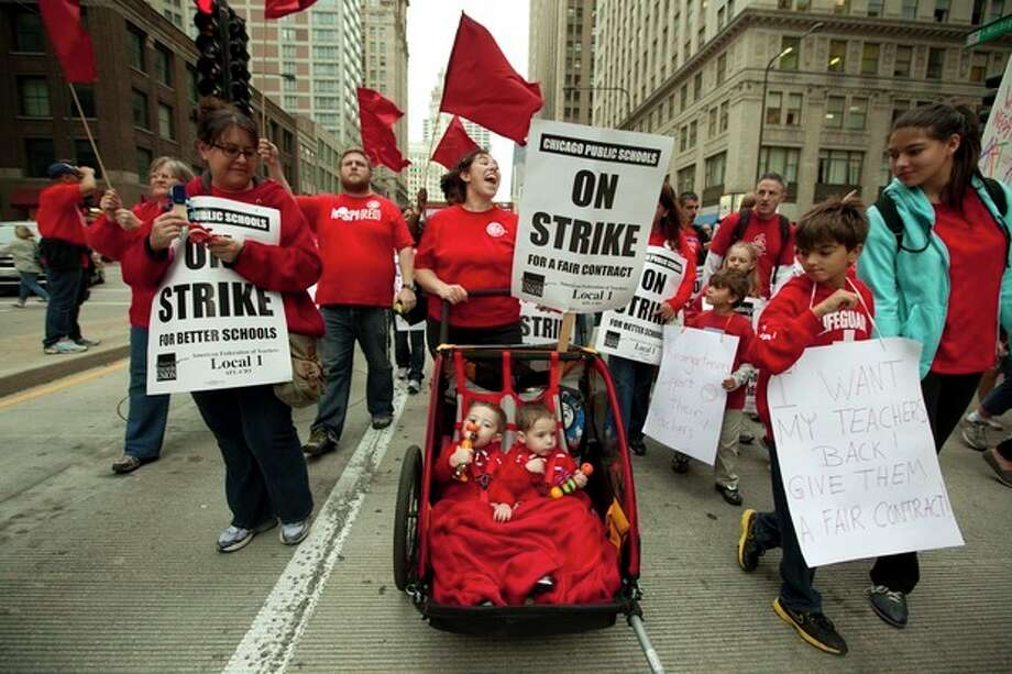 Two-year-old identical twins Colton and Lucas Jordan join thousands of public school teachers and their supporters as they march along Chicago's Michigan Avenue, protesting against Penny Pritzker, whom they accuse of benefiting from her position on the boards of both the Chicago Board of Education and Hyatt Hotels on Thursday, Sept. 13, 2012. (AP Photo/Sitthixay Ditthavong) / AP