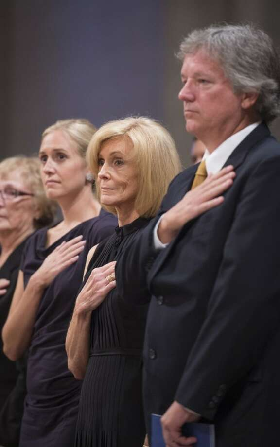 Carol Armstrong, center, her son, Eric, right, and daughter Molly Van Wagenen hold their hands to their hearts during a memorial service celebrating the life of Neil Armstrong at the Washington National Cathedral, Thursday, Sept. 13, 2012. The pioneers of space, the powerful of the capital, and the everyday public crowded into the Washington National Cathedral for a public interfaith memorial for the very private astronaut. Armstrong, who died last month in Ohio at age 82, walked on the moon in July 1969. (AP Photo/NASA, Bill Ingalls)