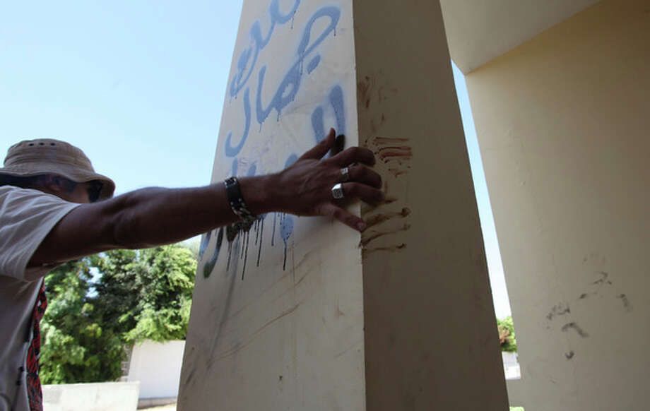 """A Libyan man explains that the bloodstains on the column are from one the American staff members who grabbed the edge of the column while he was evacuated, after an attack that killed four Americans, including Ambassador Chris Stevens on the night of Tuesday, Sept. 11, 2012, in Benghazi, Libya, Thursday, Sept. 13, 2012. The American ambassador to Libya and three other Americans were killed when a mob of protesters and gunmen overwhelmed the U.S. Consulate in Benghazi, setting fire to it in outrage over a film that ridicules Islam's Prophet Muhammad. Ambassador Chris Stevens, 52, died as he and a group of embassy employees went to the consulate to try to evacuate staff as a crowd of hundreds attacked the consulate Tuesday evening, many of them firing machine-guns and rocket-propelled grenades. Arabic writing reads, """" Villa of Jamal al Beshary"""". which was written by the owner to protect the property from another attack. (AP Photo/Mohammad Hannon) / AP"""