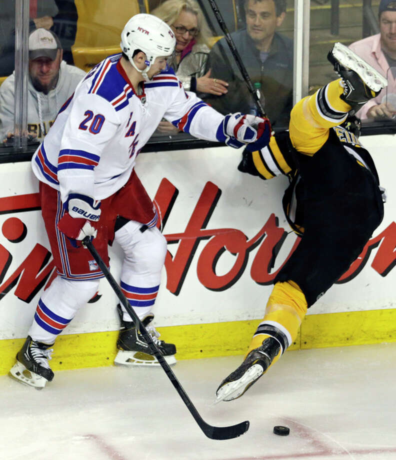 Boston Bruins defenseman Dennis Seidenberg, right, is upended by New York Rangers left wing Chris Kreider (20) during the second period in Game 5 of the Eastern Conference semifinals in the NHL hockey Stanley Cup playoffs in Boston, Saturday, May 25, 2013. (AP Photo/Charles Krupa) / AP