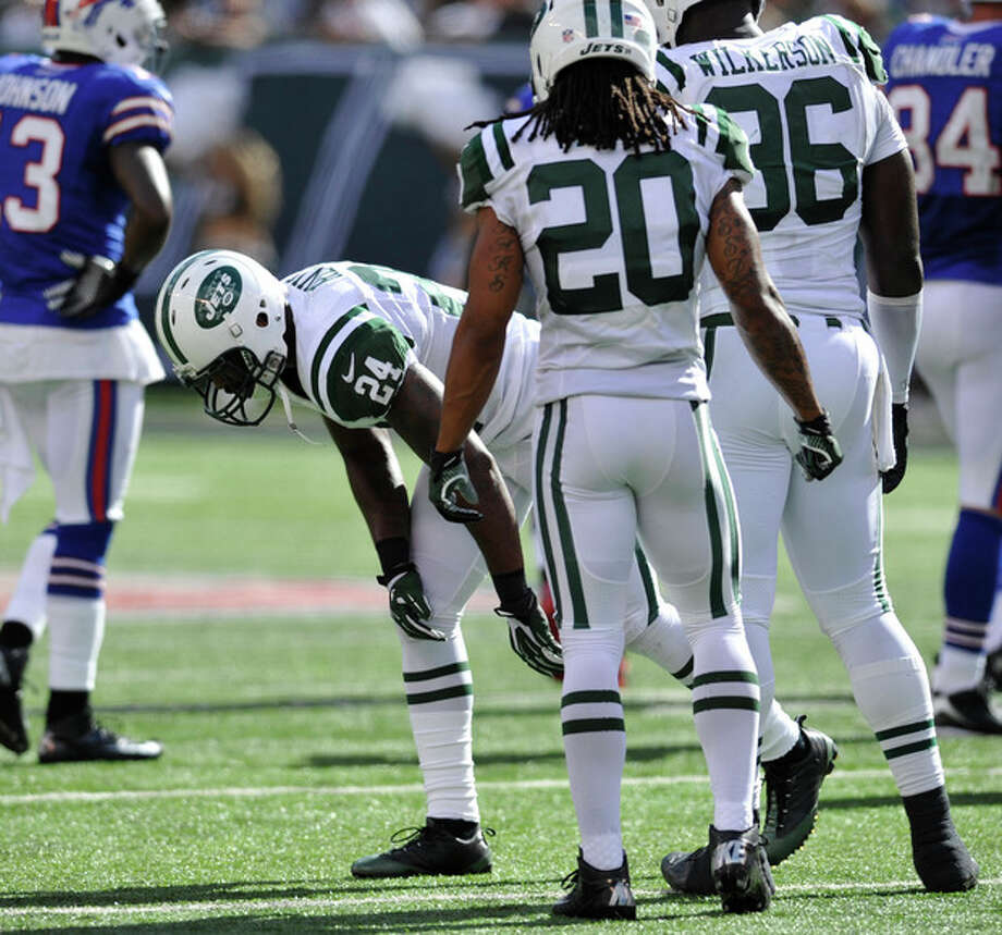 "In this Sept. 9, 2012 photo, New York Jets' Darrelle Revis (24) gets up slowly after being injured on a play during the first half of an NFL football game against the Buffalo Bills, at MetLife Stadium in East Rutherford, N.J. The star cornerback suffered what the team called a ""mild concussion."" Jets teammate Kyle Wilson (20) and Muhammed Wilkerson (96) are in the foreground. (AP Photo/Bill Kostroun) / FR51951 AP"