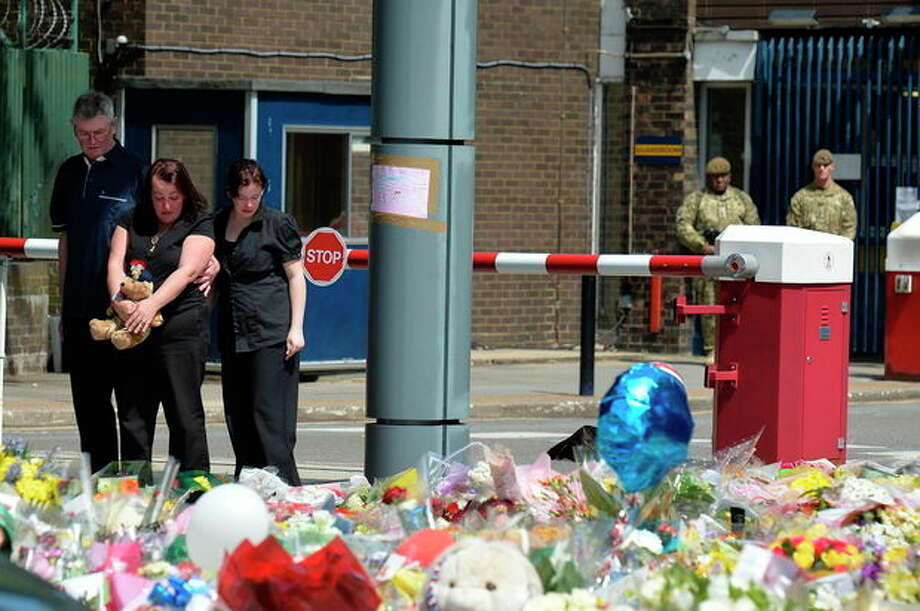 The mother of killed Drummer Lee Rigby, Lyn Rigby, centre, holds onto a teddy bear as she joins his stepfather Ian, and other family members looking at floral tributes outside Woolwich Barracks as they visit the scene of his murder in Woolwich, south-east London, Sunday May 26, 2013. Family members laid flowers at the Woolwich Barracks where the 25-year-old soldier of the Royal Regiment of Fusiliers Lee Rigby was attacked and killed by two men in broad daylight Wednesday May 22, and where hundreds of floral tributes have been left by public well wishers. (AP Photo / John Stillwell, PA) UNITED KINGDOM OUT - NO SALES - NO ARCHIVES / PA
