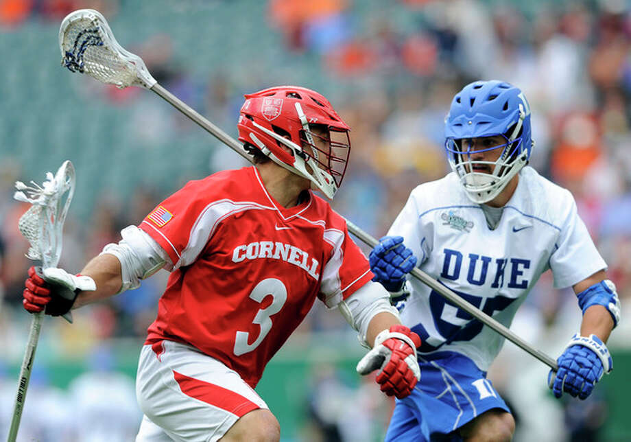 Cornell's Rob Pannell (3) drives past Duke's Bill Conners (55) during the first half of an NCAA division 1 semifinal lacrosse game on Saturday, May 25, 2013, in Philadelphia. (AP Photo/Michael Perez) / FR168006 AP