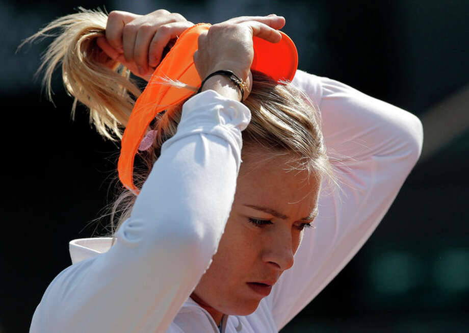 Russia's Maria Sharapova adjusts her cap during a training session for the 2013 French Open tennis tournament, at Roland Garros stadium in Paris, Saturday May, 25, 2013. (AP Photo/Christophe Ena) / AP