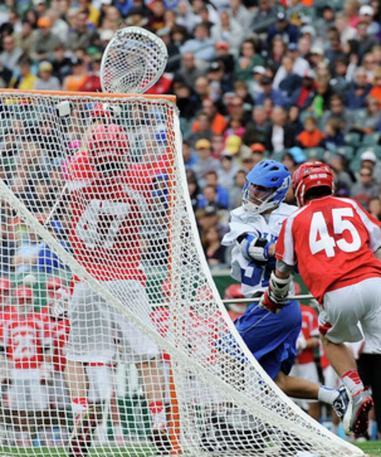 Duke's Jordan Wolf, middle, shoots and scores a goal around Cornell's Jason Noble (45) and AJ Fiore (47) during the first half of an NCAA division 1 semifinal lacrosse game on Saturday, May 25, 2013, in Philadelphia. (AP Photo/Michael Perez) / FR168006 AP