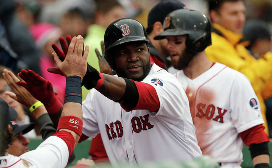 Boston Red Sox's David Ortiz, center, and Dustin Pedroia, right, are greeted at the dugout after they both scored on a single by Daniel Nava during the eighth inning of their 7-4 win over the Cleveland Indians in a baseball game at Fenway Park in Boston, Saturday, May 25, 2013. (AP Photo/Winslow Townson) / FR170221 AP