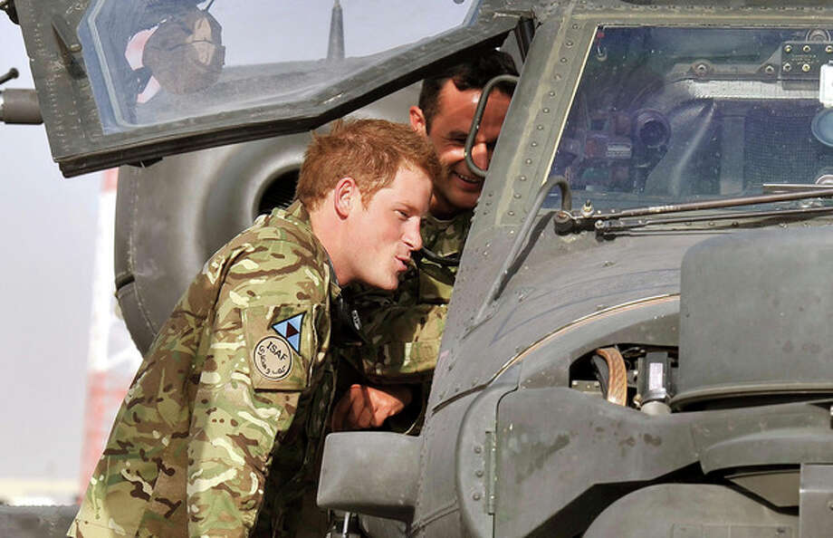 FILE - Photo dated 7/9/2012 of Britain's Prince Harry examining the cockpit of an Apache helicopter with a member of his squadron (name not provided) at Camp Bastion in Afghanistan, where he will be operating from during his tour of duty as a co-pilot gunner. The prince was unharmed after an attack on the Camp Bastion compound in which two US Marines were killed and several more wounded Saturday Sept. 15, 2012. US officials said the attack last night was by heavily-armed insurgents and involved a range of weaponry, including mortars, rockets or rocket-propelled grenades, as well as small arms fire. Harry was about two kilometres away with other crew members of the Apache attack helicopters, when the attack took place, sources said. (AP Photo/John Stillwell/pool file) / PA pool