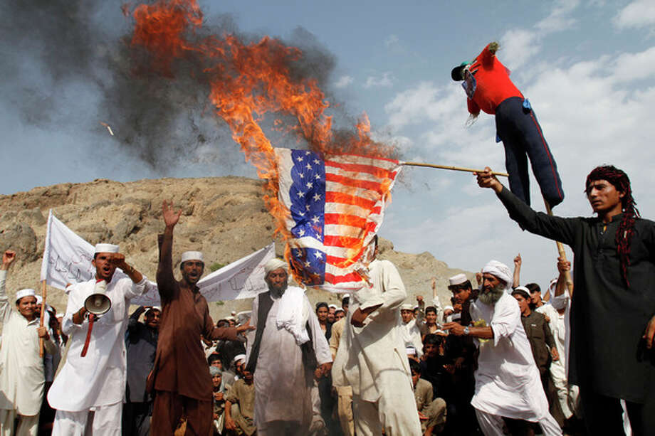 Afghans burn the U.S. flag in Ghanikhel district of Nangarhar province, east of Kabul, Afghanistan, Friday, Sept. 14, 2012 during a protest against an anti-Islam film which depicts the Prophet Muhammad as a fraud, a womanizer and a madman. (AP Photo/Rahmat Gul) / AP