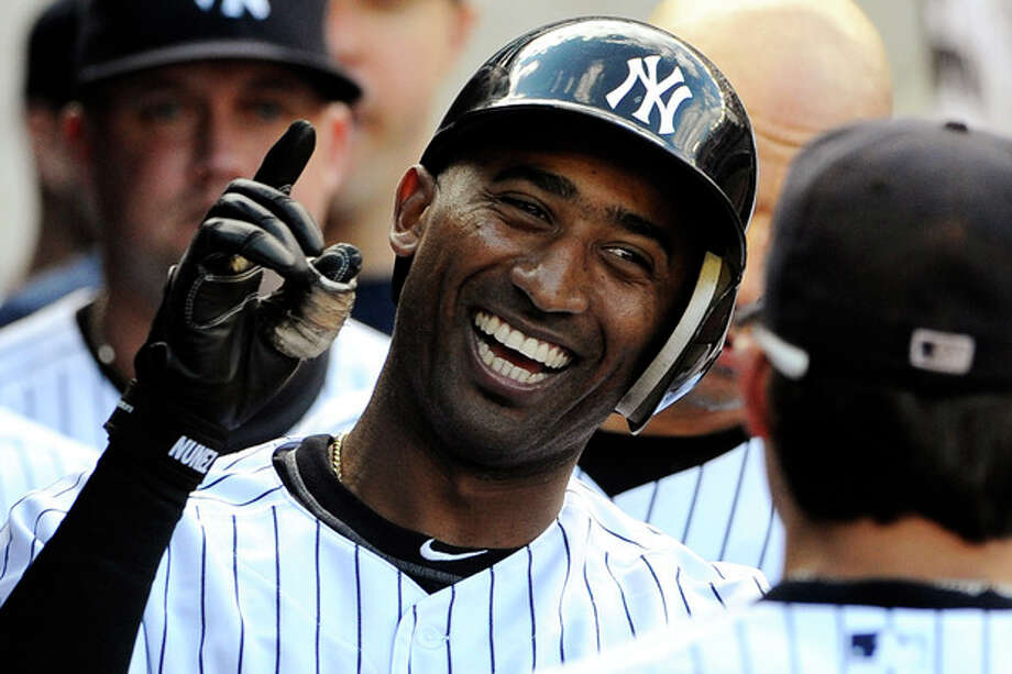 New York Yankees' Eduardo Nunez celebrates with teammates in the dugout after hitting a solo home run off of Tampa Bay Rays starting pitcher James Shields in the second inning of a baseball game, Saturday, Sept. 15, 2012, at Yankee Stadium in New York. (AP Photo/Kathy Kmonicek) / FR170189 AP