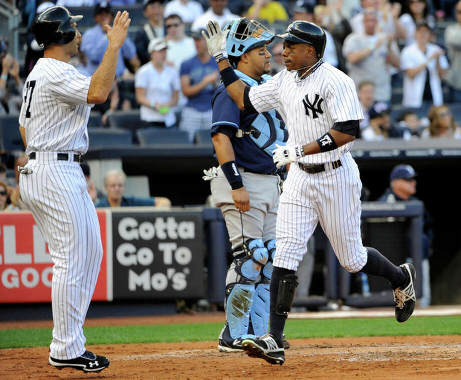 New York Yankees' Curtis Granderson, right, runs past Tampa Bay Rays catcher Jose Molina to high-five Raul Ibanez (27) after hitting a two-run home run off of Rays' James Shields that scored Ibanez in the second inning of a baseball game, Saturday, Sept. 15, 2012, at Yankee Stadium in New York. (AP Photo/Kathy Kmonicek) / FR170189 AP