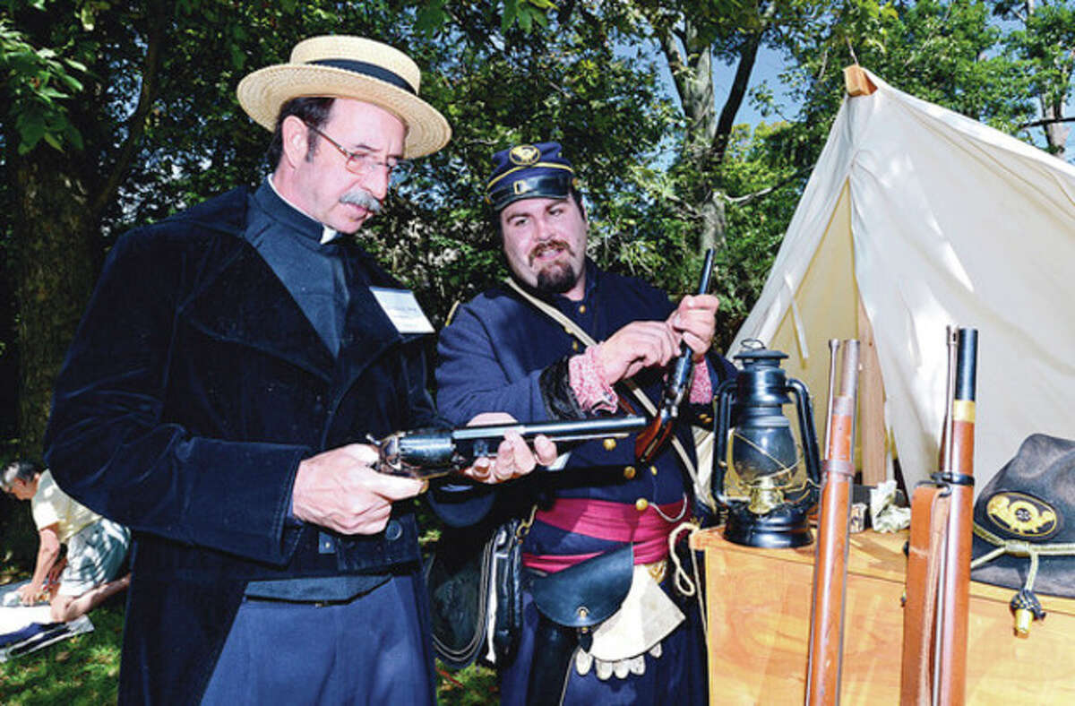 Renactors Roberty Hard and Justin Pianka look over period weaponry during the Rowayton Historical Society sponsored Civil War encampment at Pinkney Park Saturday where kids 6 and up to had the opportunity to be a trained like a union soldier as well as experience, music, a Civil War exhibit, and have a visit from Abe Lincoln and other historic characters. Hour photo / Erik Trautmann