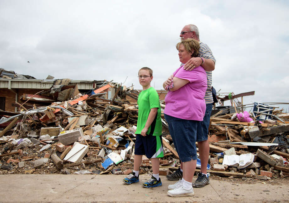 Julie Lewis watches with her husband Scott Lewis, and their son Zack, as President Barack Obama moves on with his tour of the devastation of Moore, Okla., after trying to comfort them Sunday, May 26, 2013. Zack was a third-grader at the Plaza Towers Elementary School, now reduced to rubble in the background after the devastating tornado and severe weather last week. (AP Photo/Carolyn Kaster) / AP