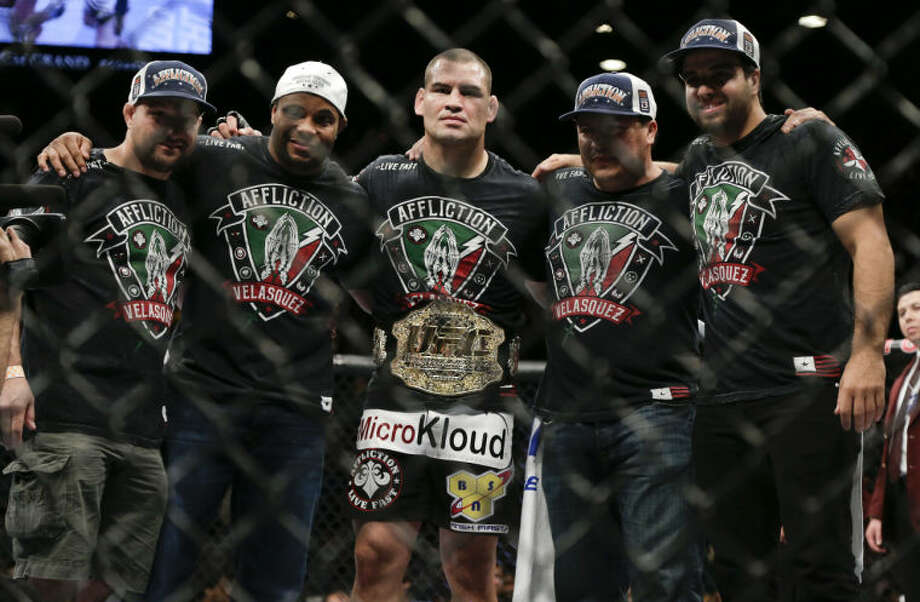 Cain Velasquez, center, poses with his UFC 160 mixed martial arts heavyweight title belt after beating Antonio Silva by technical knockout in the first round, Saturday, May 25, 2013, in Las Vegas. (AP Photo/Julie Jacobson)