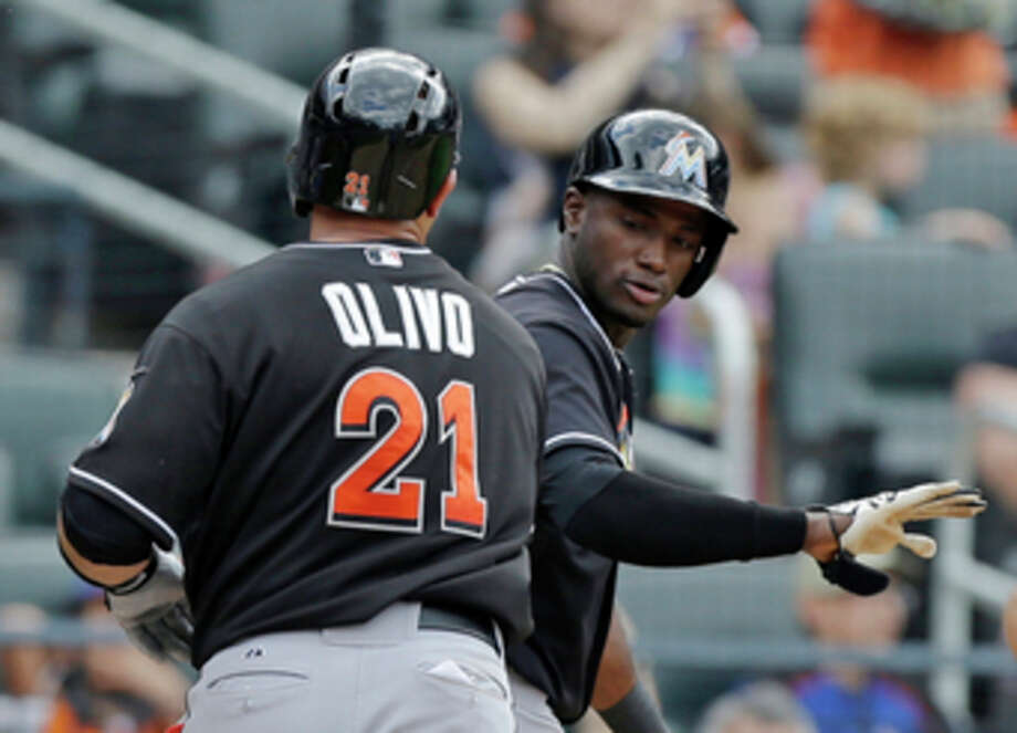 Miami Marlins Adeiny Hechavarria congratulates Marlins Miguel Olivo (21) after scoring on Olivo's tenth-inning, two-run home run off New York Mets relief pitcher Robert Carson in a baseball game in New York, Sunday, June 9, 2013. (AP Photo/Kathy Willens) / AP