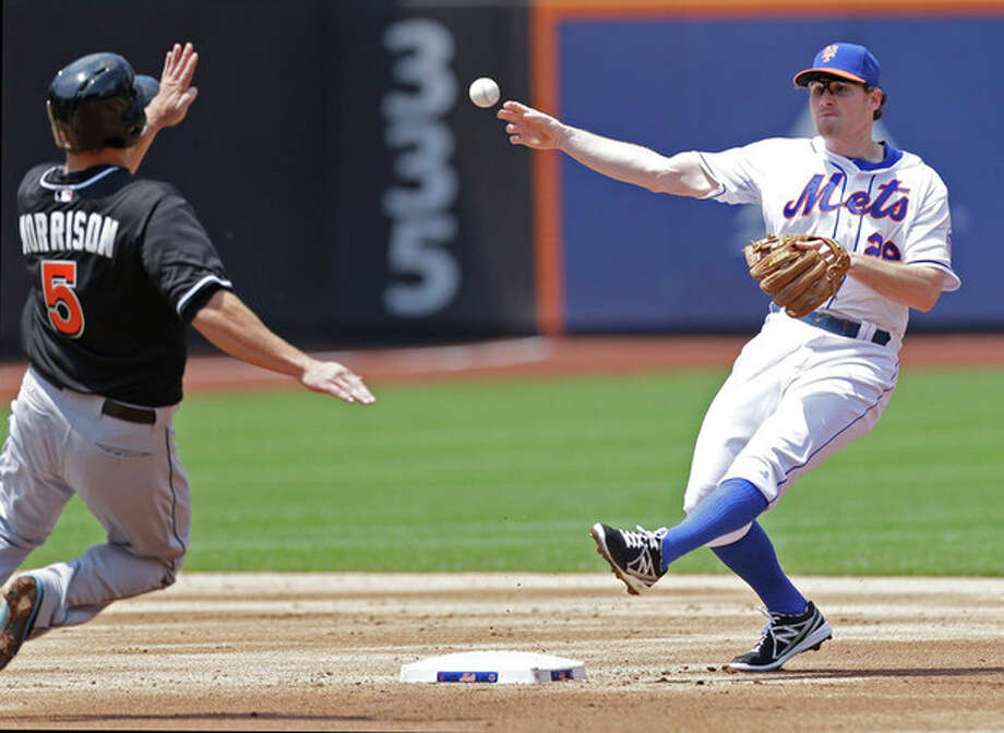 New York Mets second baseman Daniel Murphy (28) throws to first after forcing out Miami Marlins' Logan Morrison (5) when Marlins' Justin Ruggiano grounded into a second-inning double play in a baseball game in New York, Sunday, June 9, 2013. (AP Photo/Kathy Willens) / AP