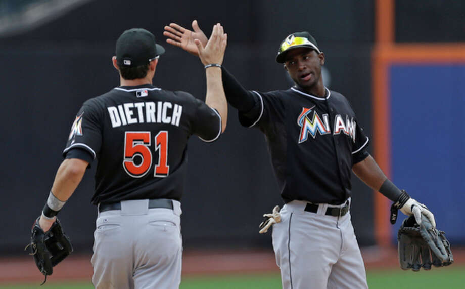 Miami Marlins shortstop Adeiny Hechavarria, right, celebrates the Marlins 8-4 victory over the New York Mets with Miami Marlins second baseman Derek Dietrich (51) at the conclusion of their baseball game in New York, Sunday, June 9, 2013. (AP Photo/Kathy Willens) / AP