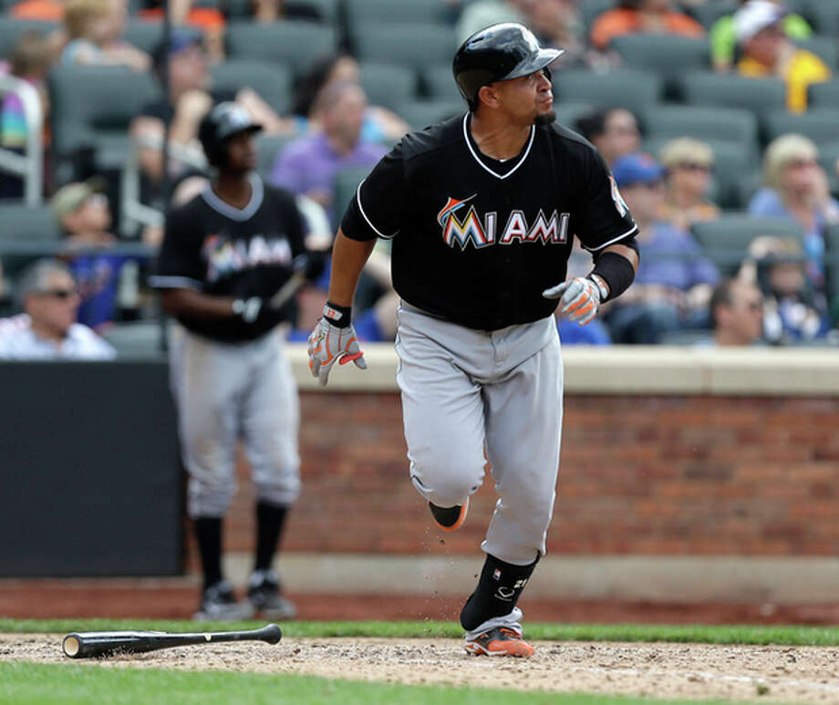 Miami Marlins Miguel Olivo watches his tenth-inning, two-run, home run off New York Mets relief pitcher Robert Carson in the Marlins 8-4 victory over the Mets in a baseball game in New York, Sunday, June 9, 2013. (AP Photo/Kathy Willens) / AP