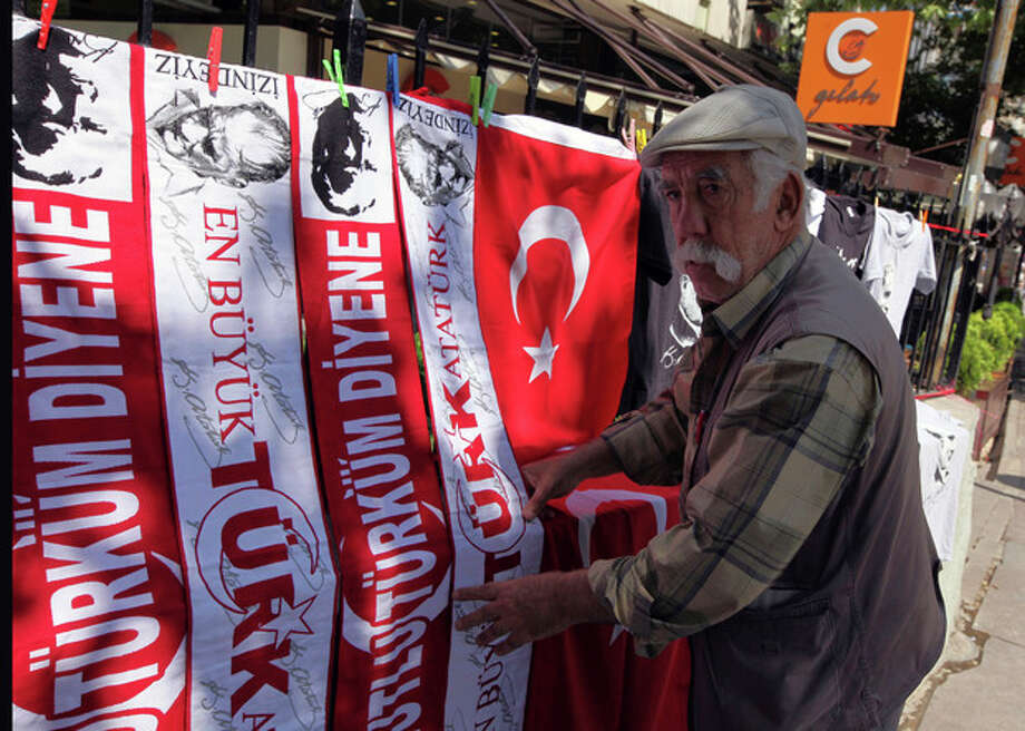 AP Photo/Burhan OzbiliciA street vendor adjusts his flags and banners with portraits of Turkey's founder Kemal Ataturk that reads: 'Happy is the person who calls himself a Turk', in Ankara's Kugulu Park, Sunday June 9. / AP
