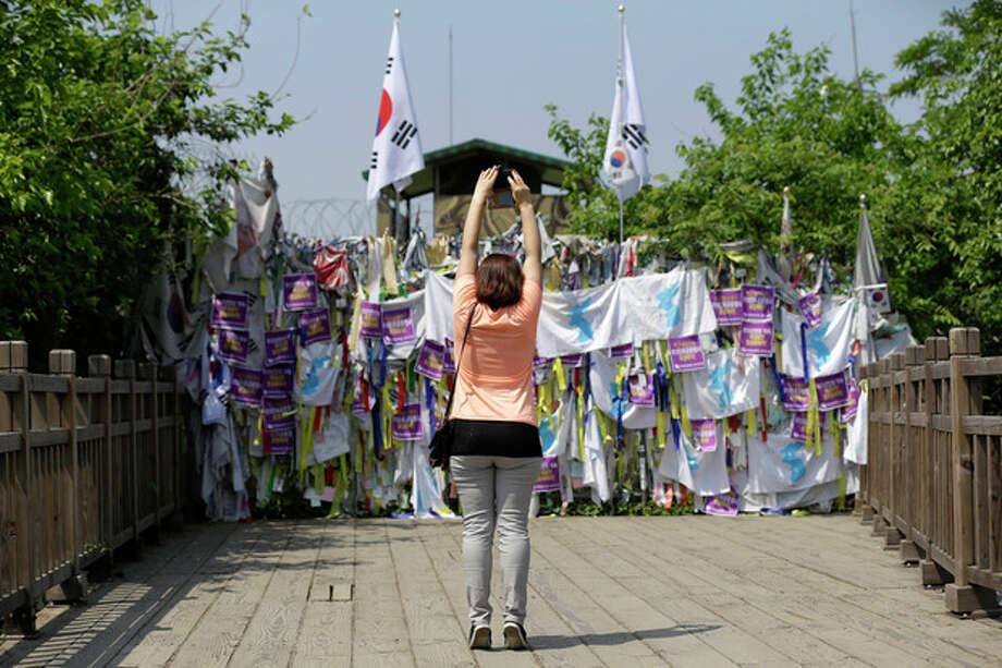"A visitor stands on their toes while taking souvenir photos in front of a wire fence covered with ribbons carrying messages left by visitors wishing for the reunification of the two Koreas, at the Imjingak Pavilion near the border village of Panmunjom, which has separated the two Koreas since the Korean War, in Paju, north of Seoul, South Korea, Sunday, June 9, 2013. Government delegates from North and South Korea began preparatory talks Sunday at Panmunjom, a ""truce village"" on their heavily armed border aimed at setting ground rules for a higher-level discussion on easing animosity and restoring stalled rapprochement projects. (AP Photo/Lee Jin-man) / AP"