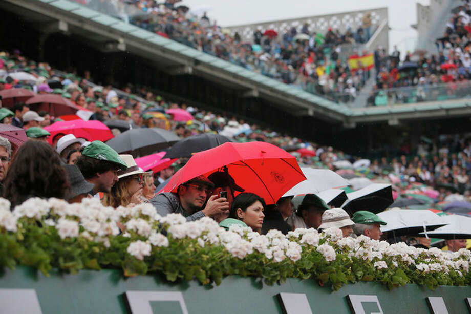 A spectator under a red umbrella takes images with a smart phone as Spain's Rafael Nadal returns against compatriot David Ferrer in the final of the French Open tennis tournament, at Roland Garros stadium in Paris, Sunday June 9, 2013. (AP Photo/Michel Spingler) / AP