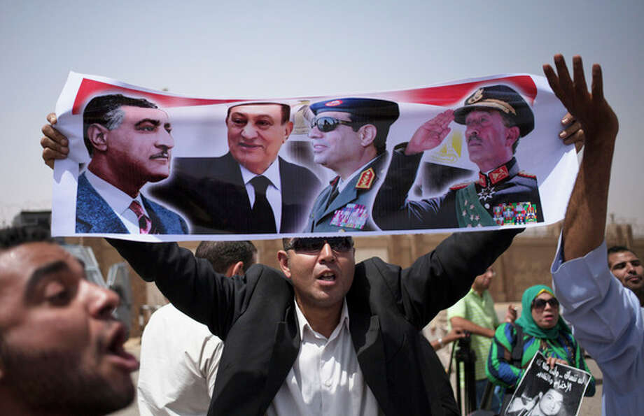 Supporters holding pictures of Egypt's ousted President Hosni Mubarak rally outside a courtroom in Cairo Saturday, June 8, 2013. (AP Photo/Khalil Hamra) / AP