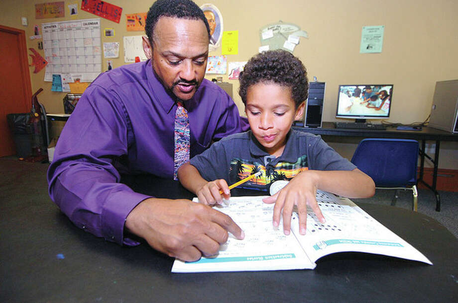Hour photo / Alex von KleydorffGregory Riley works with six-year-old Jordy Garcia on his Growing with Mathematics workbook at the Meadow Gardens Community Center recently. / 2012 The Hour Newspapers