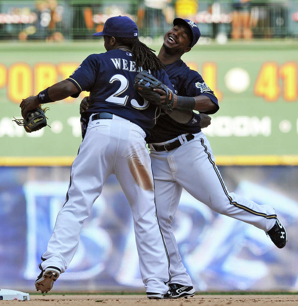 Milwaukee Brewers' Rickie Weeks (23) and Jean Segura celebrate the Brewers 3-0 victory over the New York Mets after a baseball game, Sunday, Sept. 16, 2012, in Milwaukee. (AP Photo/Jim Prisching)