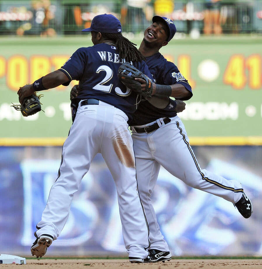 Milwaukee Brewers' Rickie Weeks (23) and Jean Segura celebrate the Brewers 3-0 victory over the New York Mets after a baseball game, Sunday, Sept. 16, 2012, in Milwaukee. (AP Photo/Jim Prisching) / FR59933 AP