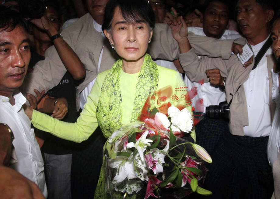 Myanmar opposition Leader Aung San Suu Kyi, center, arrives at Yangon International airport to leave for United State Sunday, Sept. 16 2012, in Yangon. Suu Kyi leaves Sunday on her first U.S. trip since she was put under house arrest in 1990. (AP Photo/Khin Maung Win) / AP