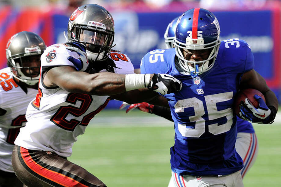 New York Giants running back Andre Brown (35) stiff-arms Tampa Bay Buccaneers strong safety Mark Barron (24) during the second half of an NFL football game, Sunday, Sept. 16, 2012, in East Rutherford, N.J. (AP Photo/Bill Kostroun) / FR59151 AP