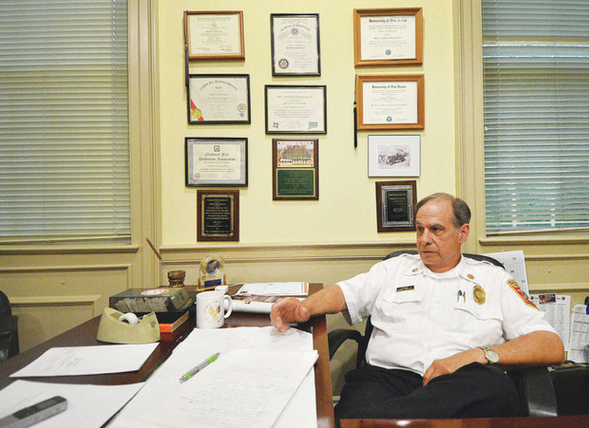 Hour photo / Alex von Kleydorff Norwalk Fire Marshal Glenn Iannaccone, surrounded by photos and awards in his office, announces his retirement.