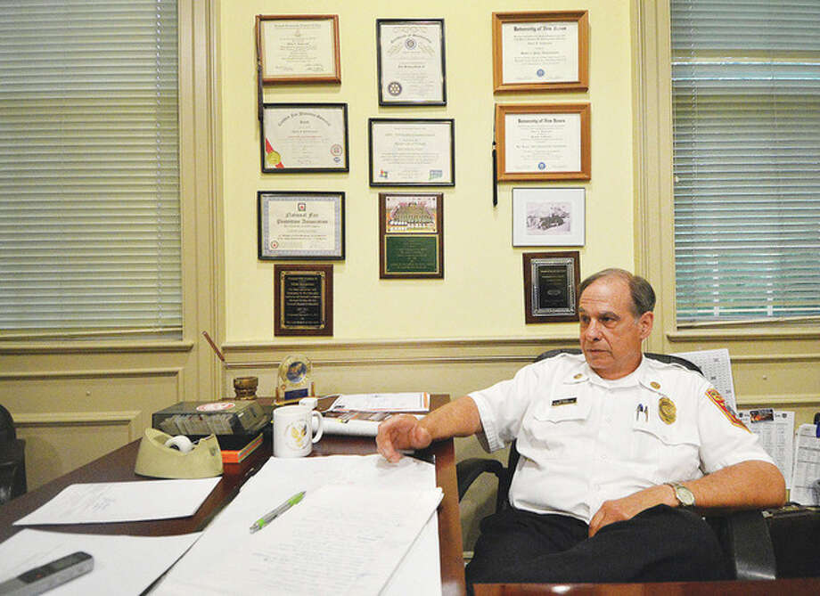 Hour photo / Alex von KleydorffNorwalk Fire Marshal Glenn Iannaccone, surrounded by photos and awards in his office, announces his retirement.