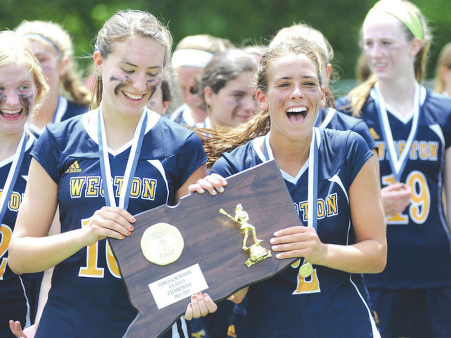 Hour photo/John NashWeston's Fran Holmes, left, and Morgan Moubayed take possession of the Class S girls lacrosse championship trophy following the Trojans' 13-8 win over Haddam-Killingworth on Sunday in Stratford.