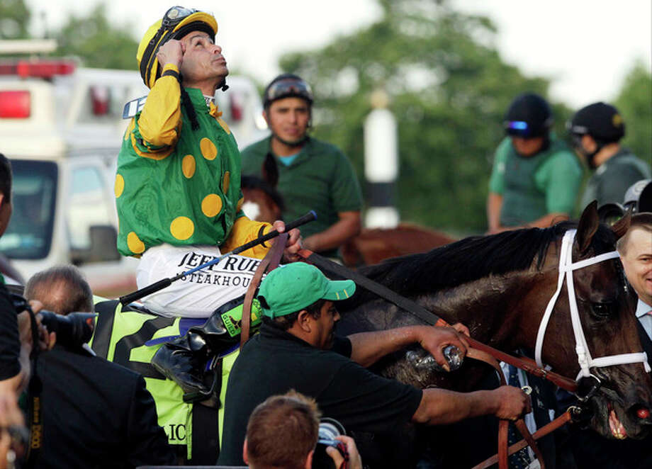 jockey Mike Smith looks skyward and celebrates after riding Palace Malice to win the 145th Belmont Stakes horse race at Belmont Park Saturday, June 8, 2013, in Elmont, N.Y. (AP Photo/Mark Lennihan) / AP