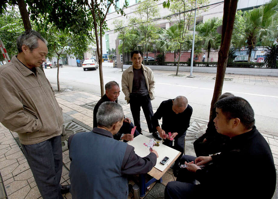 UPDATING THE CAPTION WHEN THE TRIAL STARTED - Chinese people play cards on the pavement near the Chengdu Intermediate People's Court in Chengdu in southwest China's Sichuan province Monday, Sept. 17, 2012. The trial of Wang Lijun, an ex-police chief at the center of China's worst political scandal in decades, started unexpectedly at the court Monday, a day earlier than the court had announced. At the height of his career, Wang led a police crackdown on the violent underworld in a sprawling metropolis, arresting hundreds of gangsters and government officials, some of whom were sentenced and executed in a matter of months. Now the former police chief is in the hands of the opaque Chinese justice he once brandished against others. (AP Photo/Andy Wong) / AP