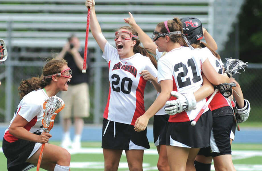 Hour photo/John NashNew Canaan's Olivia Hompe, left, joins the celebration with teammates Elizabeth Burke (20) and Abigail Sawabini (21) after the final buzzer in the Rams 10-6 win over Wilton in the Class M championship game.