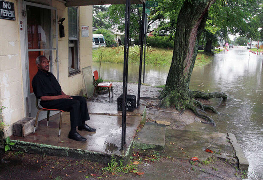 Lee Tillery sits on the porch of his Singletary Street home surrounded by flooded streets in Wilson, N.C.,after heavy rains sweep across the region, Friday, June 7, 2013. Tropical Storm Andrea moved quickly across south Georgia and was leaving the Carolinas waterlogged on Friday while sparing the area any serious damage. (AP Photo/ The Wilson Times, Gray Whitley) / Gray Whitley