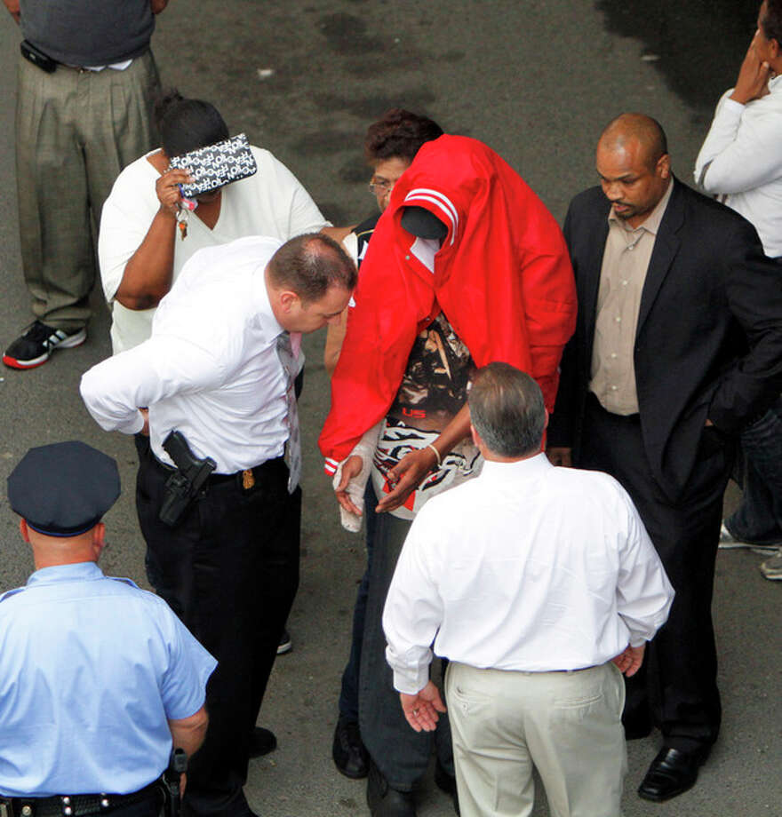 Sean Benschop, center, with a red jacket over his head, holds out his hands for investigators as he arrives at the Philadelphia Police Department's Central Detectives Division, Saturday June 8, 2013, in Center City Philadelphia. Benschop, the heavy equipment operator with a lengthy rap sheet accused of being high on marijuana when a downtown building collapsed onto a thrift store, killing six people, turned himself in on Saturday to face charges in the deaths, police said. (AP Photo/ Joseph Kaczmarek) / FR109827 AP