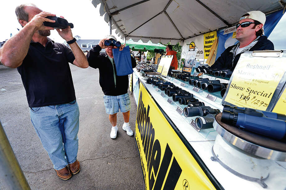 Ben Cracco and Steve Auletta test some binoculars with the help of Shark Tested Optics sales associate Andrew Carton at the 2012 Norwalk Boat Show Thursday at Cove Marina. Hour photo / Erik Trautmann / (C)2012, The Hour Newspapers, all rights reserved