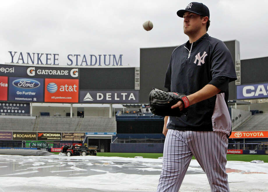 New York Yankees starting pitcher Phil Hughes tosses a ball as he leaves the tarp-covered field after throwing on flat ground after their baseball game against the Toronto Blue Jays was postponed because of inclement weather, Tuesday, Sept. 18, 2012, at Yankee Stadium in New York. The teams will play a day-night doubleheader Wednesday. (AP Photo/Kathy Willens) / AP