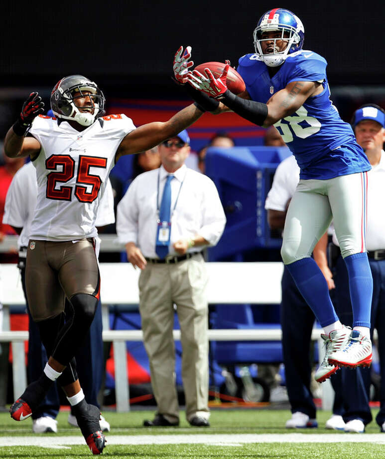 New York Giants wide receiver Hakeem Nicks (88) completes a pass in front of Tampa Bay Buccaneers cornerback Aqib Talib (25) during the first half of an NFL football game, Sunday, Sept. 16, 2012, in East Rutherford, N.J. (AP Photo/Julio Cortez) / AP