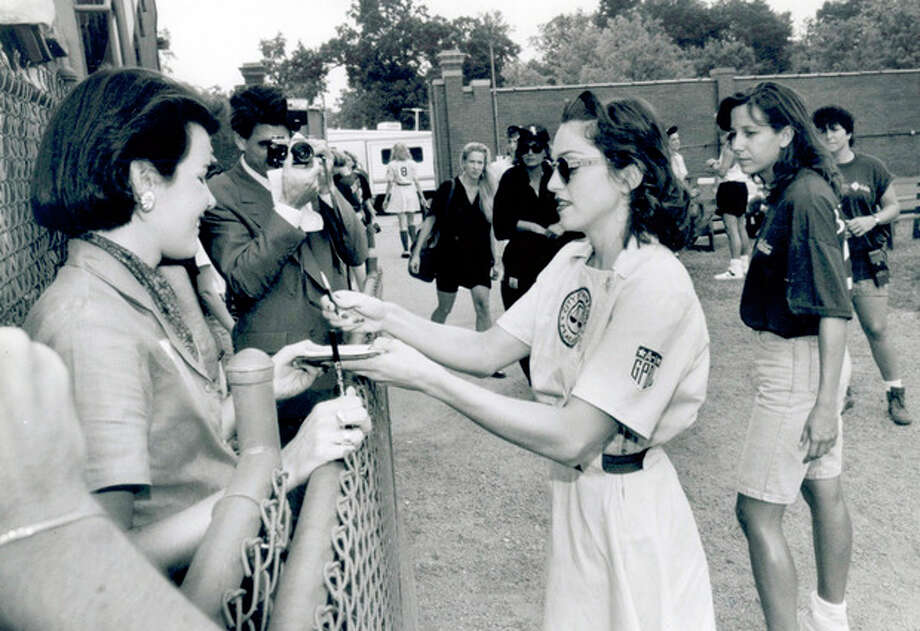 """FILE - This Sept. 9, 1991 file photo, shows Madonna, right, signing autographs for members of the media during filming of """"A League of Their Own"""" at Bosse Field in Evansville, Ind. (AP Photo/The Evansville Courier & Press) / The Evansville Courier & Press"""