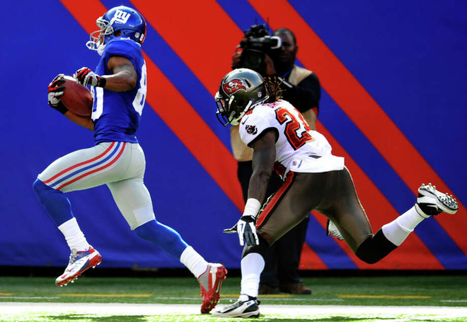 New York Giants' Hakeem Nicks (88) runs away from Tampa Bay Buccaneers' Mark Barron (24) for a touchdown during the second half of an NFL football game, Sunday, Sept. 16, 2012, in East Rutherford, N.J. (AP Photo/Bill Kostroun) / FR59151 AP