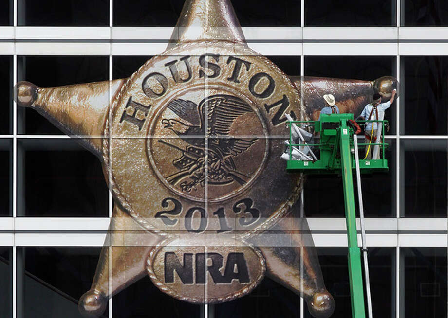 The National Rifle Association logo is placed on the George R. Brown Convention Center by Lynn Creel, left, and Don Reynolds of Display Graphics on Wednesday, May 1, 2013, in Houston. The 2013 NRA Annual Meetings and Exhibits is scheduled to being Friday. (AP Photo/Houston Chronicle, Johnny Hanson) / Houston Chronicle