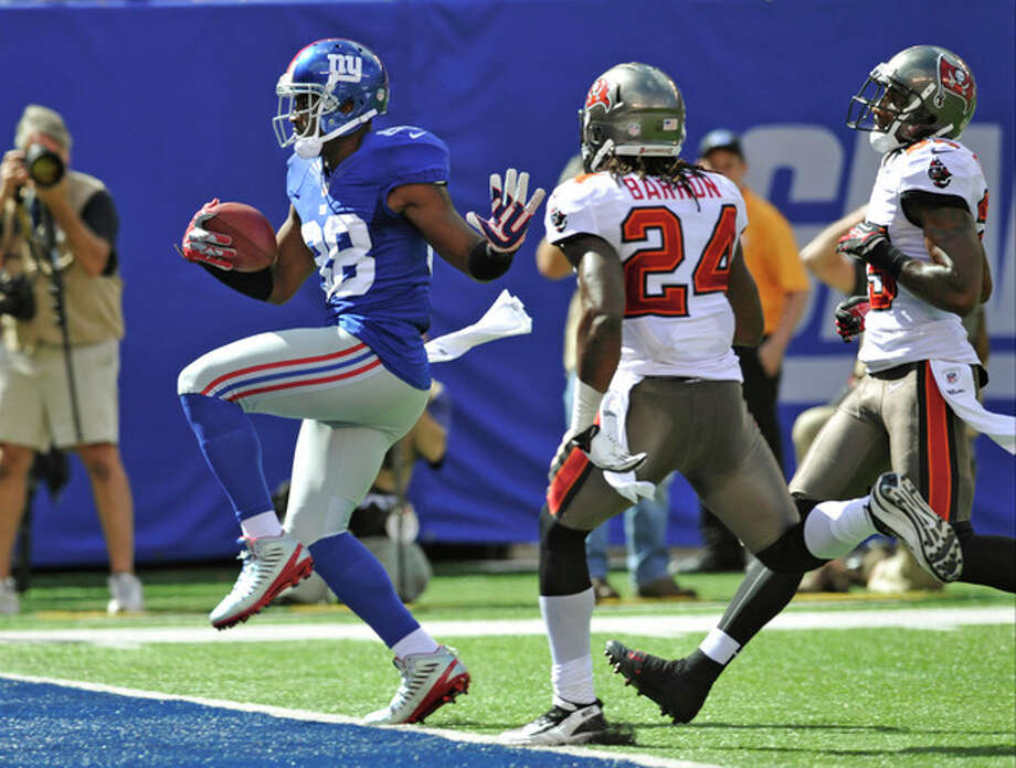 New York Giants wide receiver Hakeem Nicks (88) runs past Tampa Bay Buccaneers strong safety Mark Barron (24) for a touchdown during the first half of an NFL football game on Sunday, Sept. 16, 2012, in East Rutherford, N.J. (AP Photo/Bill Kostroun) / FR59151 AP